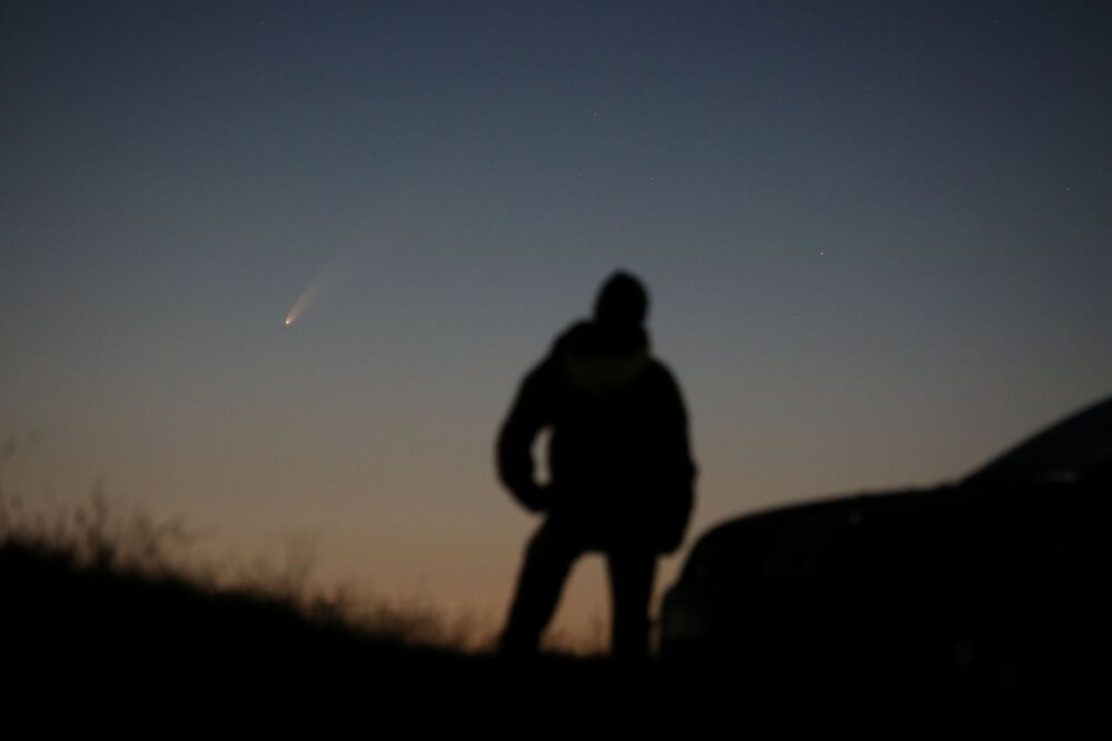 Homem observa cometa C/2020, também conhecido como NEOWISE, cruzando o céu de Ballintoy, no Reino Unido