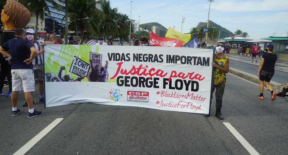 Manifestantes exibem cartaz contra o racismo durante ato no Rio de Janeiro