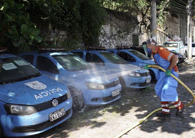 Em meio à pandemia da COVID-19, um funcionário da prefeitura desinfeta carros da polícia militar na favela do Andaraí, no Rio de Janeiro, em 13 de abril de 2020