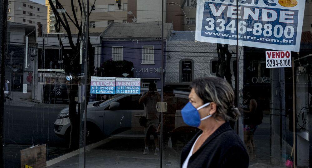 Mulher com máscara caminha em frente a um espaço comercial com placa de aluga na região central da cidade de São Paulo, em 16 de julho de 2020.
