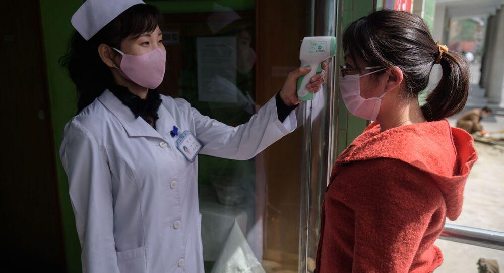 Agente sanitário mede temperatura de mulher na porta de hospital em Pyongyang, Coreia do Norte