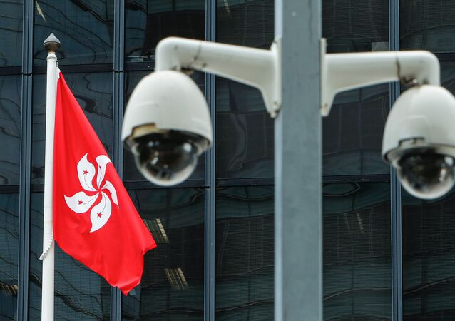 Bandeira de Hong Kong é hasteada ao lado de um par de câmeras de segurança do governo da China