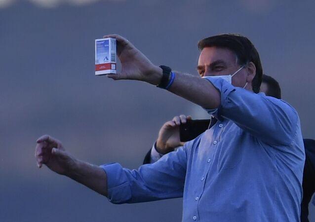 Presidente Jair Bolsonaro exibe caixa do medicamento sulfato de hidroxicloroquina durante ato em Brasília