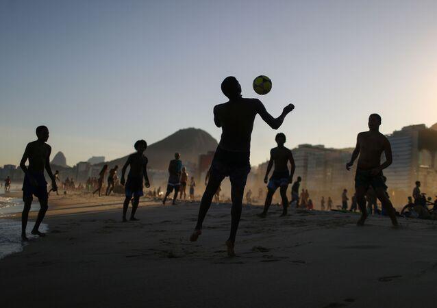 Adolescentes jogam bola na praia durante a pandemia da COVID-19 na praia de Copacabana, no Rio de Janeiro