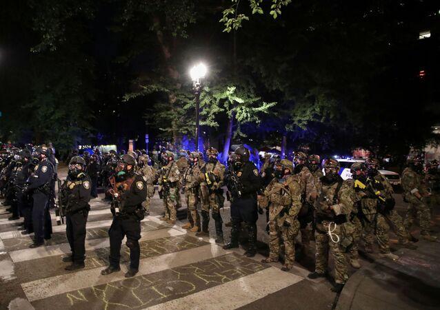 Policiais federais bloqueiam rua após retirar manifestantes da área durante manifestação contra a violência policial e a desigualdade racial em Portland, Oregon, EUA, 27 de julho de 2020