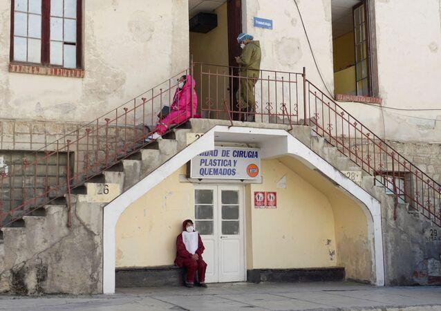 Pessoas com trajes de proteção contra coronavírus esperam por informações de parentes em hospital de Laz Paz, na Bolívia