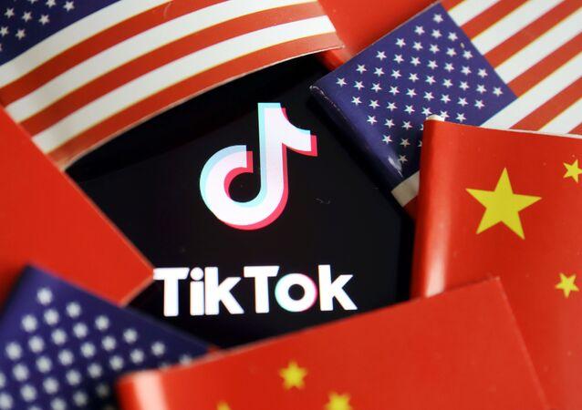 Logotipo do TikTok é representado no meio das bandeiras da China e dos EUA