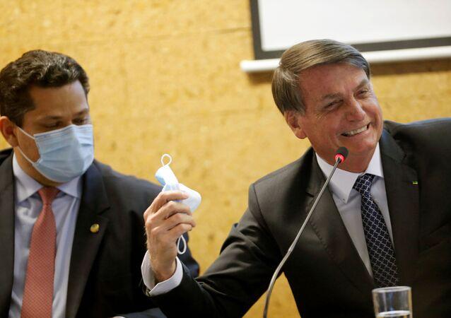 Presidente Jair Bolsonaro (à direita) e o presidente do Senado, Davi Alcolumbre, durante cerimônia de inauguração do programa Mais Luz para a Amazônia, em Brasília, 5 de agosto de 2020