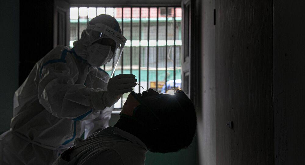 Profissional da saúde colhe amostra nasal para testes da COVID-19 em Gauhati, na Índia