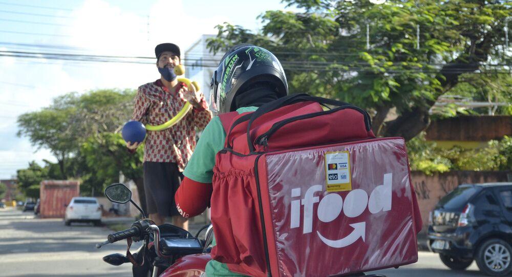 Em sinal de trânsito na avenida PE-15, em Olinda, artista de rua se apresenta e entregador de aplicativo delivery aguarda o sinal abrir