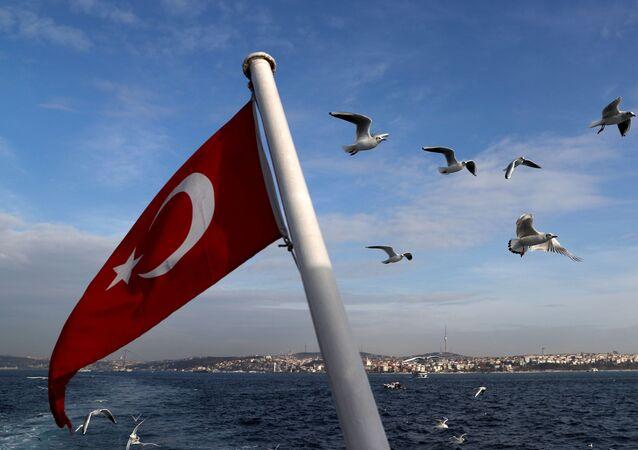 Bandeira turca voa em uma balsa de passageiros com o Bósforo ao fundo em Istambul, Turquia, 27 de janeiro de 2020