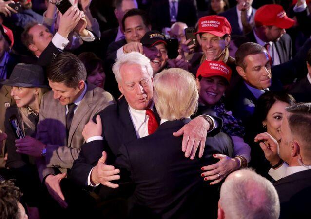 Presidente eleito dos EUA Donald Trump (de costas), abraça seu irmão Robert Trump após proferir seu discurso em Nova York, 9 de novembro de 2016