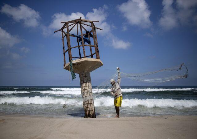 Um pescador palestino limpa sua rede de pesca em uma praia na cidade de Gaza
