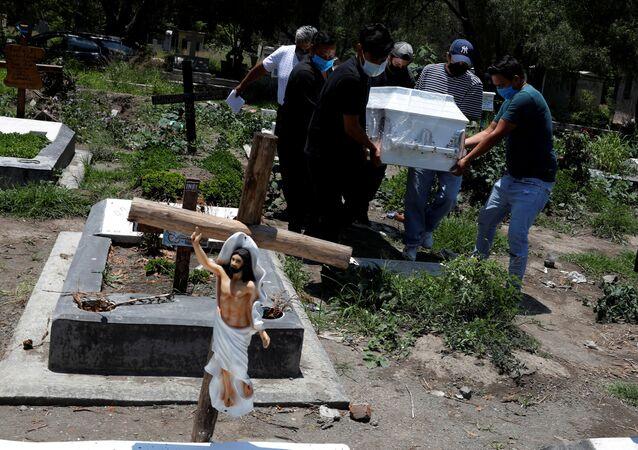 Familiares carregam caixão de vítima do coronavírus em cemitério