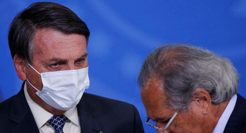 Presidente Jair Bolsonaro conversa com o ministro da Economia, Paulo Guedes, durante evento em Brasília