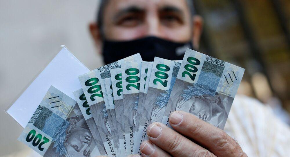 Homem mostra cédula de 200 reais após o Banco Central do Brasil emitir a nova nota, em Brasília