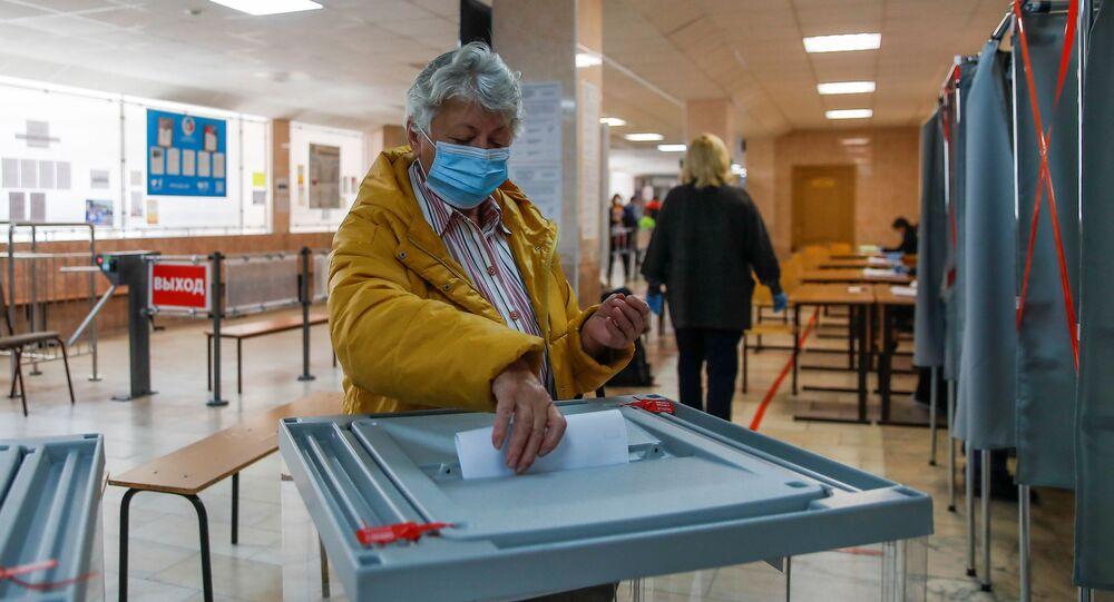 Em Tomsk, na Rússia, uma mulher deposita seu voto durante eleições locais, em 13 de setembro de 2020.