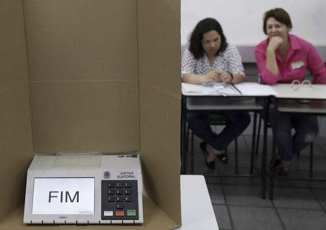 Em Brasília, uma urna eletrônica mostra a palavra Fim em uma seção eleitoral dois mesários ao fundo, em 28 de outubro de 2018.