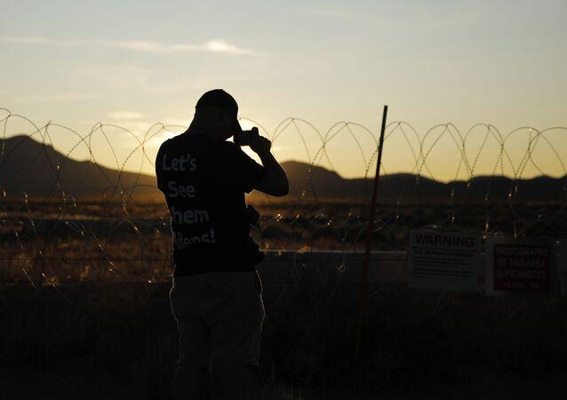 Homem tira foto de placas e arame farpado não muito longe da entrada do Campo de Testes e Treinamento de Nevada em Rachel, estado de Nevada, perto da Área 51, EUA, 20 de setembro de 2019