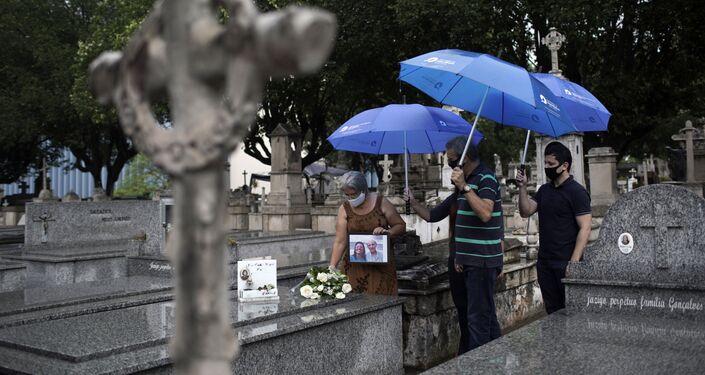 Família visita túmulo de ente querido falecido em decorrência da COVID-19, no cemitério da Penitência, no Rio de Janeiro, Brasil, 20 de setembro de 2020