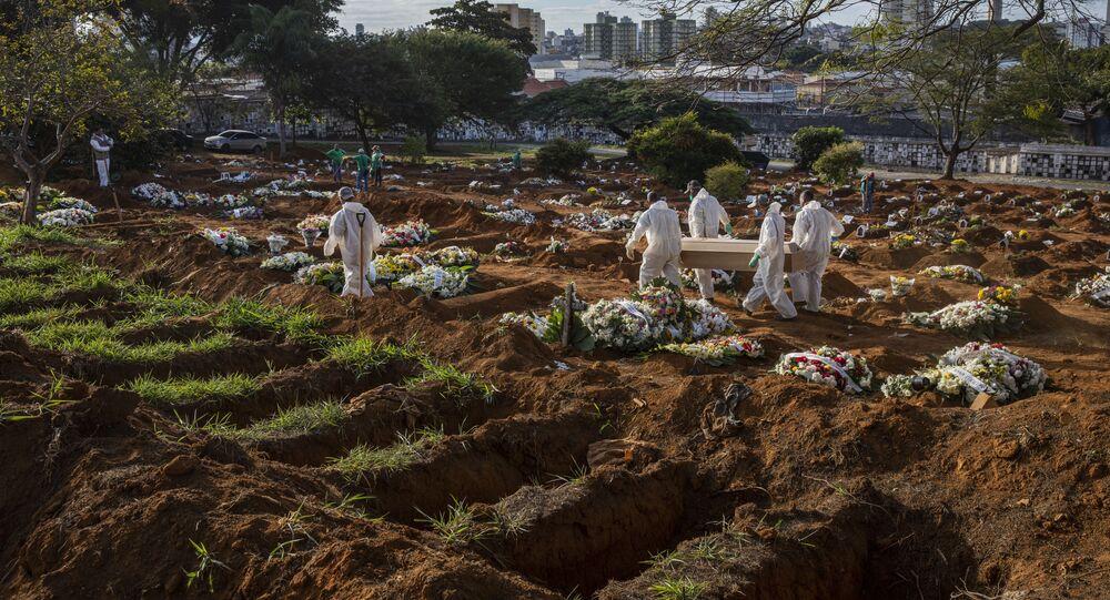 Sepultadores carregam caixão com vitima da COVID-19 no cemitério da Vila Formosa, na zona leste de São Paulo.