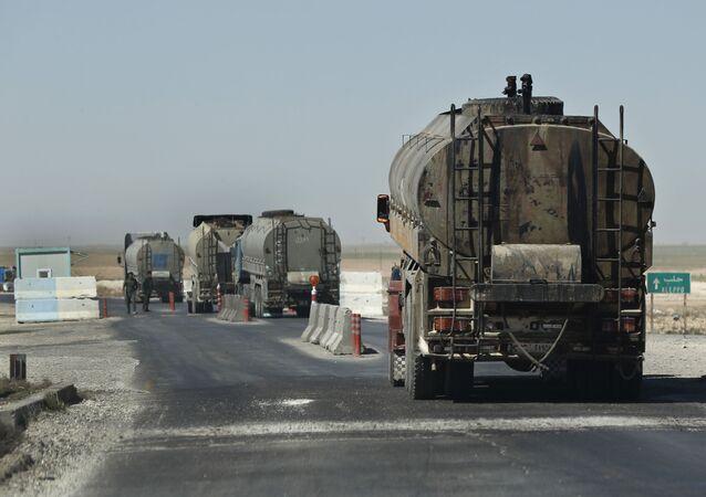Um comboio de caminhões de petróleo passa por um posto de controle da polícia curda