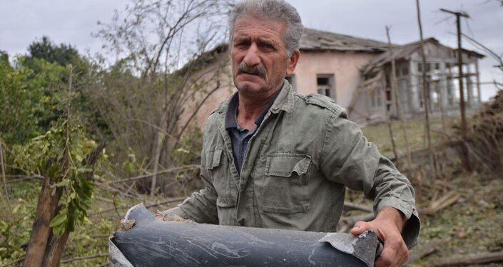 Homem segura estilhaço de munição após bombardeio por forças azeris na cidade de Martuni, em Nagorno-Karabakh