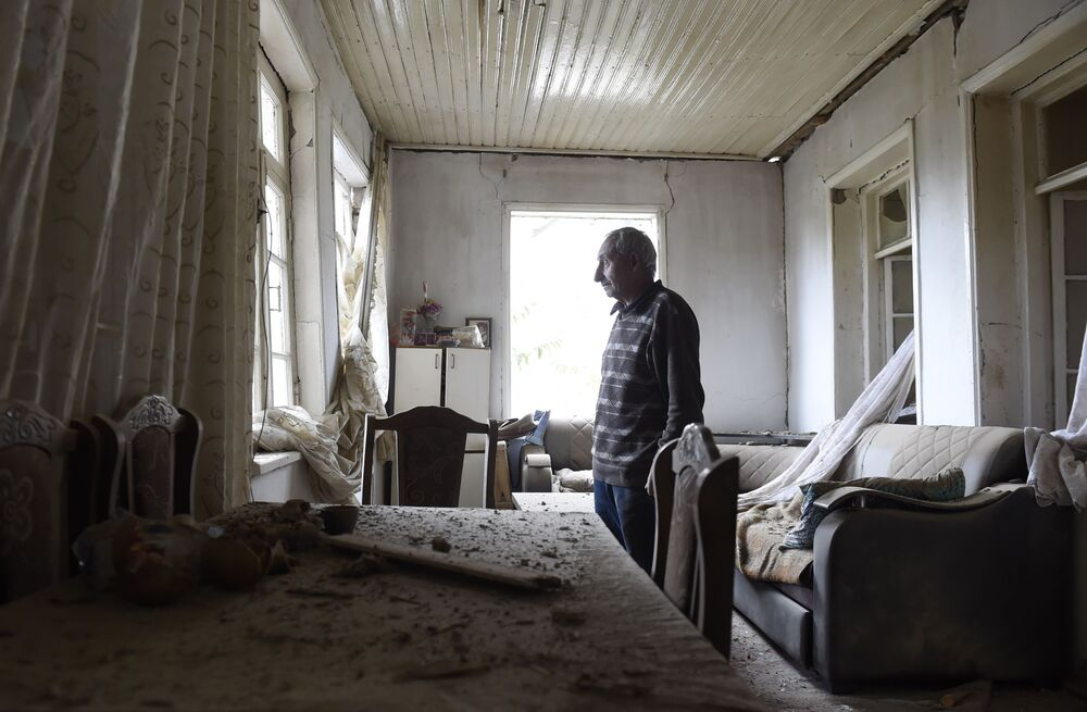 Morador da região de Nagorno-Karabakh mostra danos a sua casa provocados por bombardeio