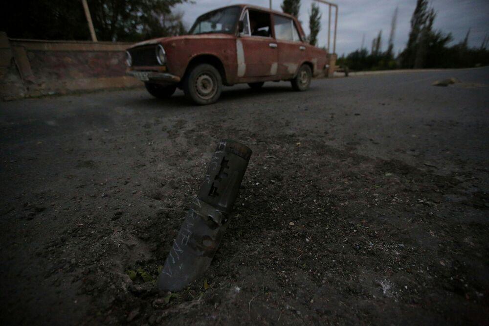 Carro passa em frente a restos de munição após a cidade de Tartar, em Nagorno-Karabakh, ser alvo de bombardeio