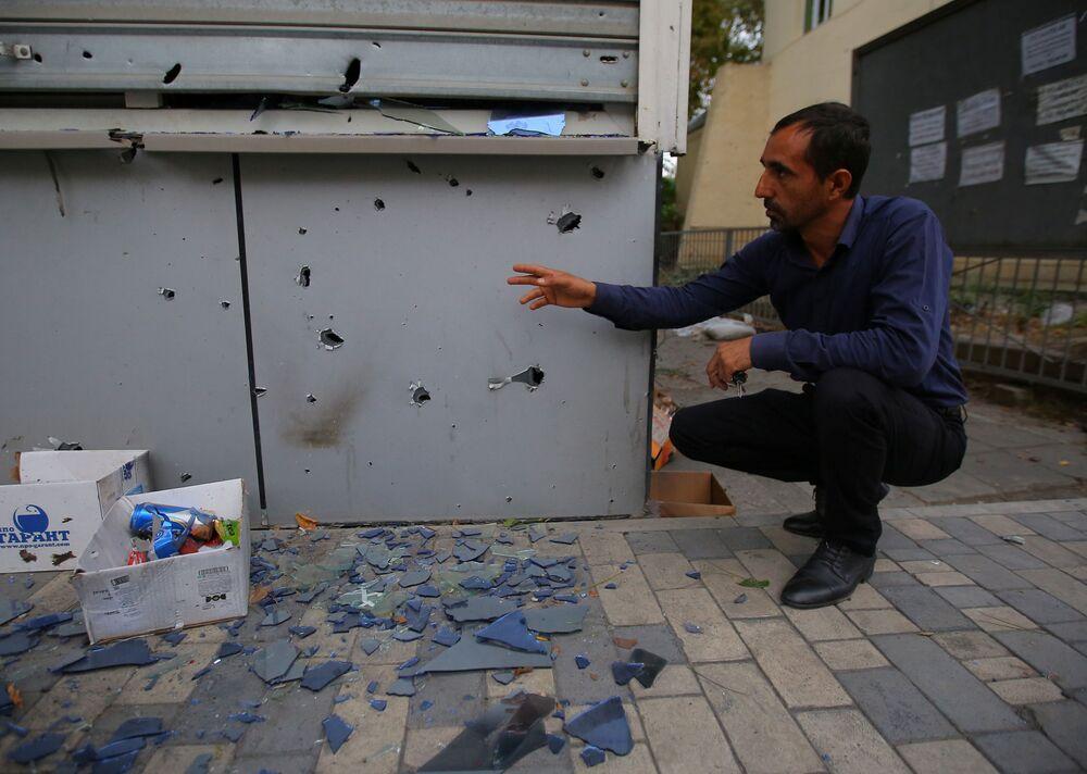 Homem mostra destruição provocada durante conflito armado na região de Nagorno-Karabakh