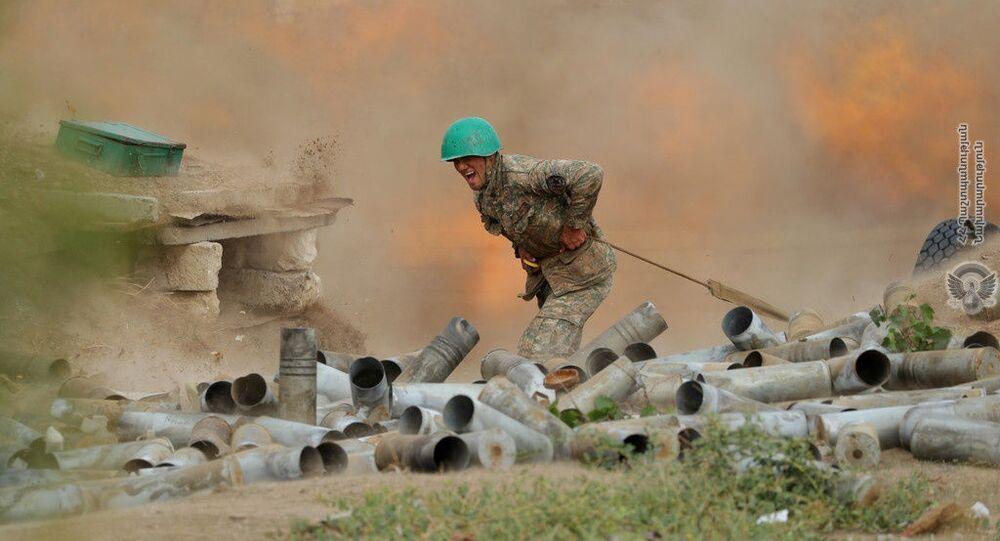 Soldado de etnia armênia dispara uma peça de artilharia durante combate contra forças do Azerbaijão na região de Nagorno-Karabakh