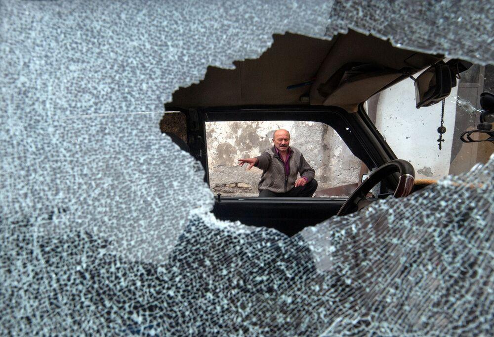 Homem diante de carro com vidros quebrados em resultado dos ataques à cidade de Stepanakert, em Nagorno-Karabakh