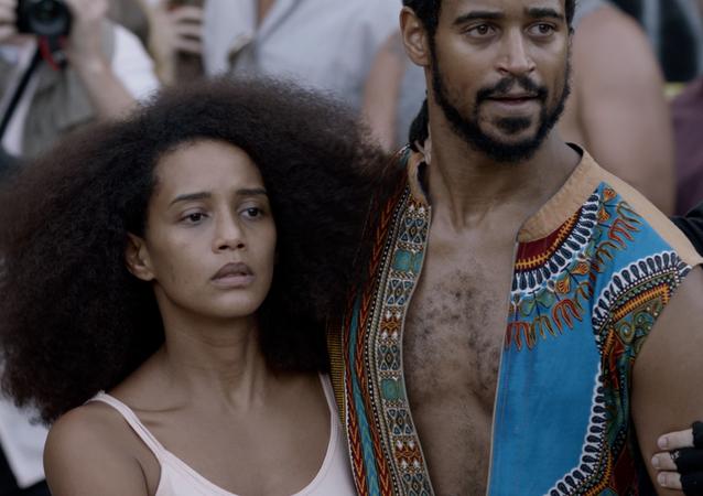 Taís Araújo e Alfie Enoch em cena do filme Medida Provisória, dirigido por Lázaro Ramos