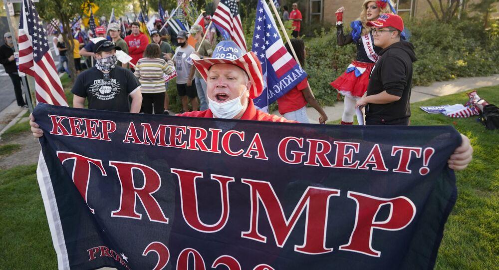 Homem segura cartaz em apoio à reeleição de Donald Trump