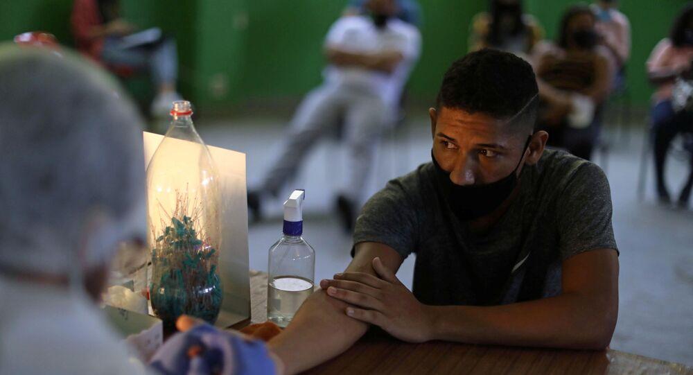 Enfermeira coleta sangue de morador para teste de COVID-19 na comunidade de Santa Marta, no Rio de Janeiro, 9 de outubro de 2020