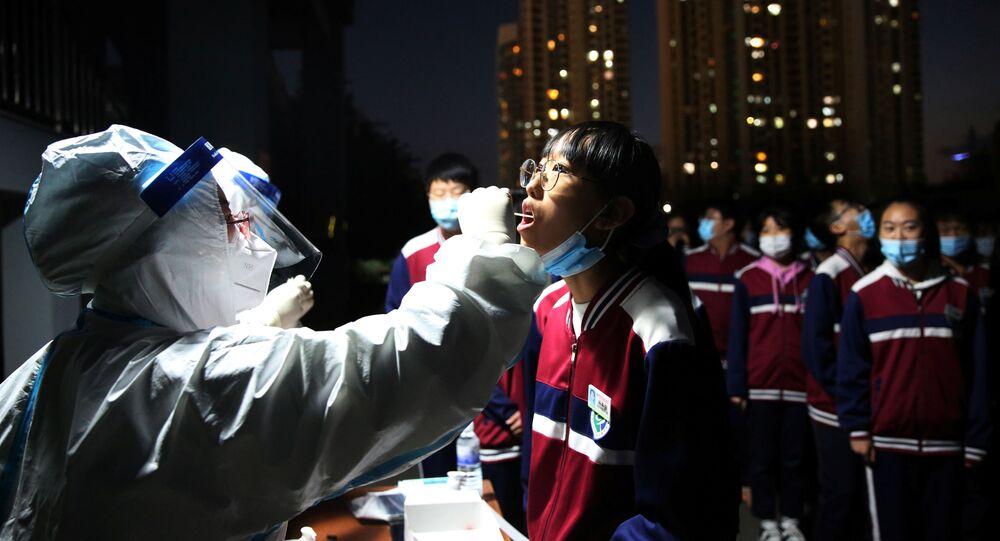 Agente de saúde coleta teste de COVID-19 de moradores da cidade chinesa de Qingdao, 12 de outubro de 2020
