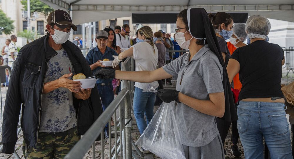 Pessoas em situação de rua fazem fila por comida em São Paulo durante a pandemia da COVID-19.