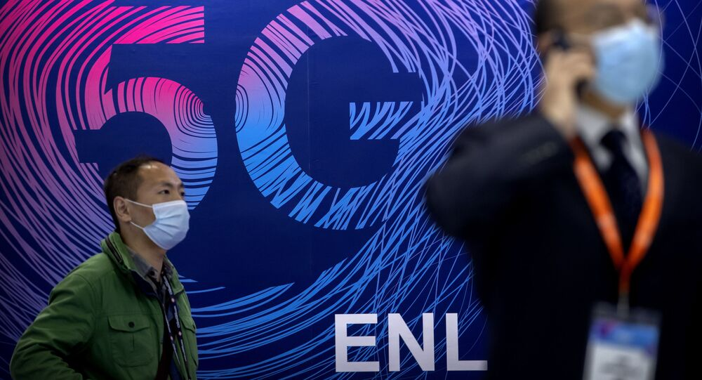 Em Pequim, na China, um homem usando máscara para proteger-se da COVID-19 passa em frente a uma propaganda da tecnologia 5G durante uma exposição, em 14 de outubro de 2020