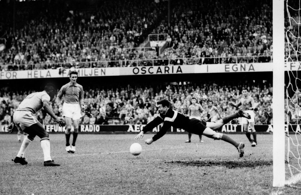 Pelé (à esquerda) se prepara quando o goleiro francês Claude Abbés perde a bola, permitindo que Pelé marque o terceiro gol do Brasil na semifinal da Copa do Mundo, em Estocolmo, Suécia, em 24 de junho de 1958. Esse dia o Brasil venceu a França por 5 a 2
