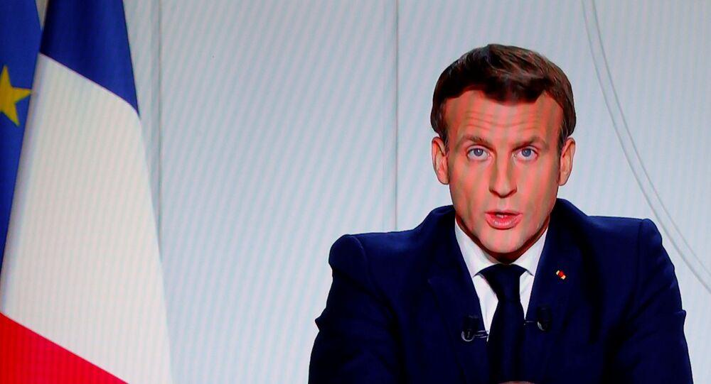 O presidente francês Emmanuel Macron é visto em uma tela durante um discurso à nação francesa anunciando novas medidas de combate à pandemia da COVID-19, em 28 de outubro de 2020