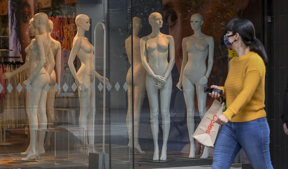 Mulher usando máscara passa em frente a vitrine com manequins em Melbourne, na Austrália