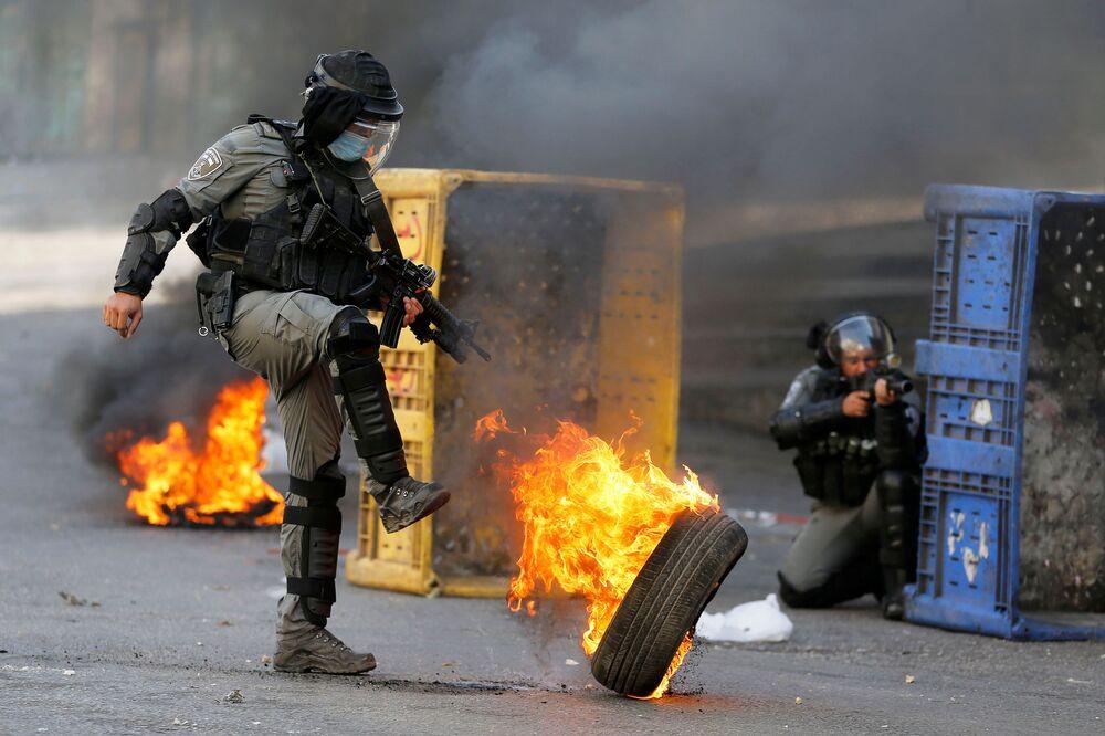 Policial de fronteira israelense chuta pneu em chamas durante protesto contra Israel promovido por palestinos em Hebron, na Cisjordânia
