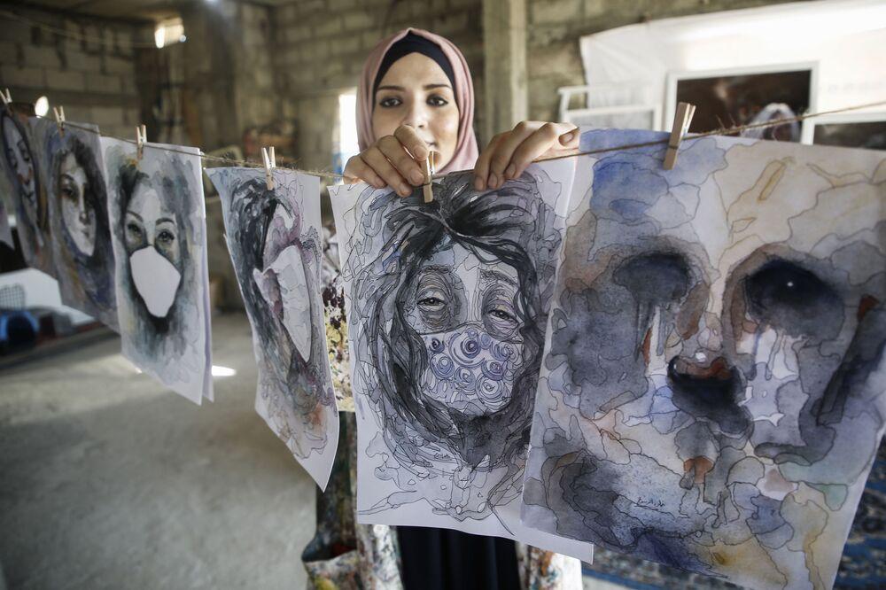 Artista palestina pendura em varal suas obras feitas em casa durante a quarentena de COVID-19 em Khan Yunis, na Faixa de Gaza