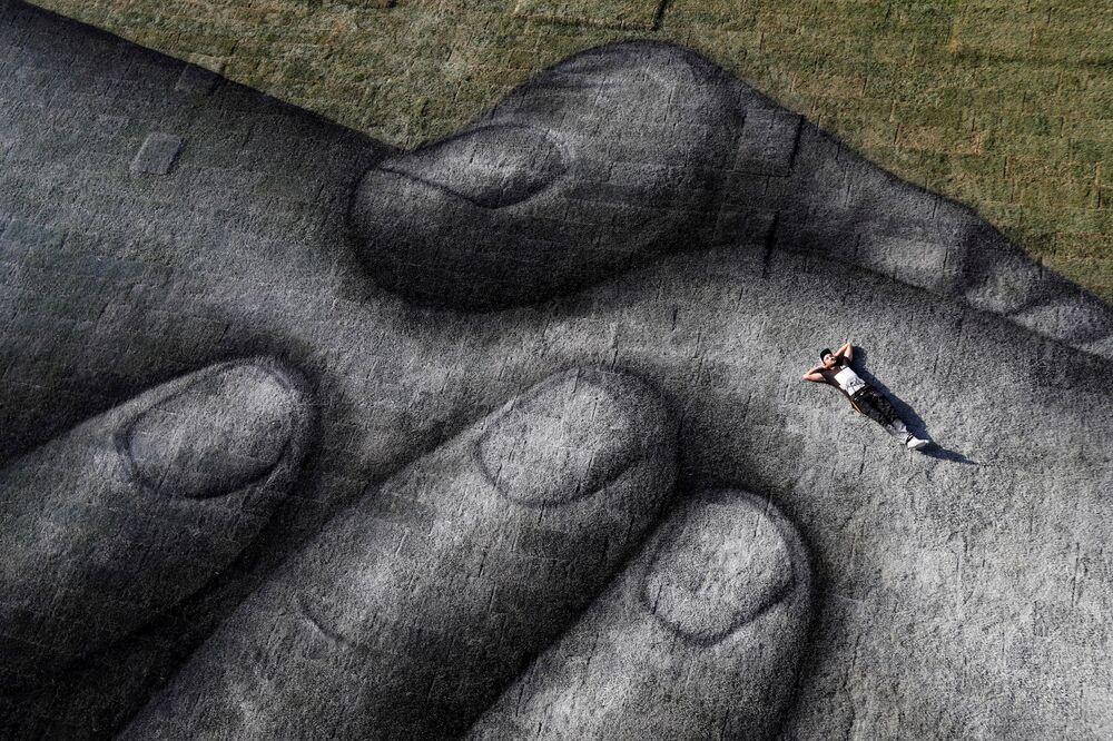 Artista de rua franco-suíço Saype posa deitado em uma de suas obras em Istambul