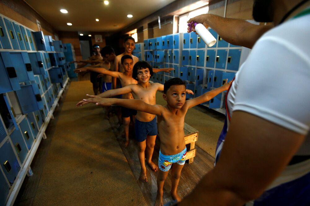 Crianças iraquianas formam fila para receber desinfecção antes de usarem uma piscina na cidade de Kerbala, Iraque