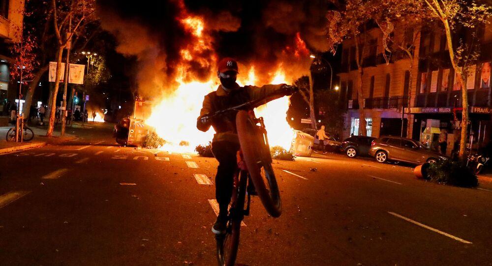 Em Barcelona, na Espanha, um homem empina uma bicicleta em frente a uma barricada em chamas durante protesto contra a quarentena da COVID-19, em 30 de outubro de 2020