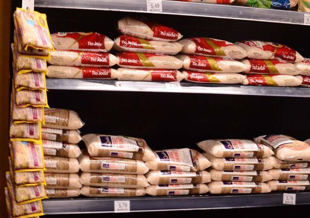 Prateleira de supermercado mostra alta no preço dos pacotes de arroz no Brasil.