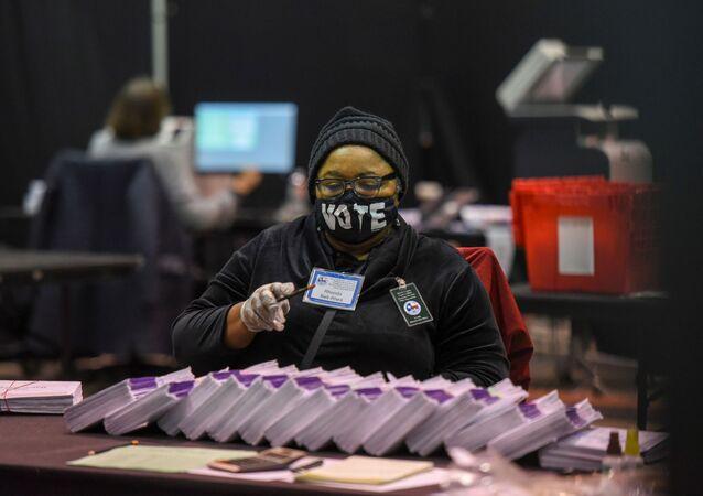 Funcionário processa cédulas eleitorais em Houston, na véspera do pleito nos Estados Unidos