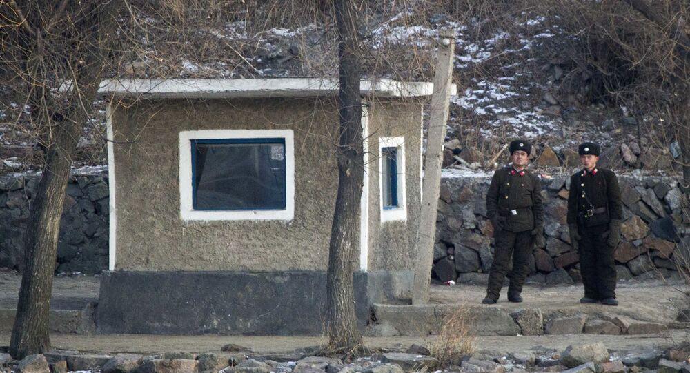 Soldados norte-coreanos tomam guarda ao longo da margem do rio que banha a cidade norte-coreana de Sinuiju, lado oposto à cidade fronteiriça chinesa de Dandong, 20 de dezembro de 2011