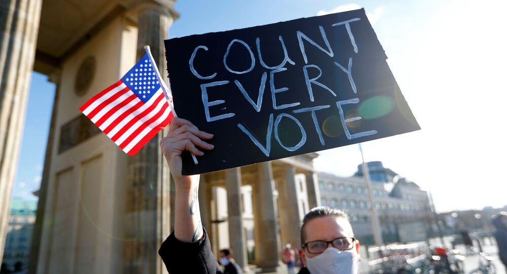 Manifestante segura bandeira dos EUA e cartaz, em manifestação organizada pelos Jovens Democratas no Exterior, com a mensagem Conte cada voto, durante as eleições presidenciais norte-americanas de 2020, junto ao Portão de Brandenburgo em Berlim, Alemanha, 4 de novembro de 2020
